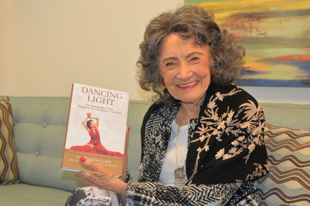96-year-old yoga master Tao Porchon-Lynch in the green room of the Steve Harvey Show holding her new book, Dancing Light