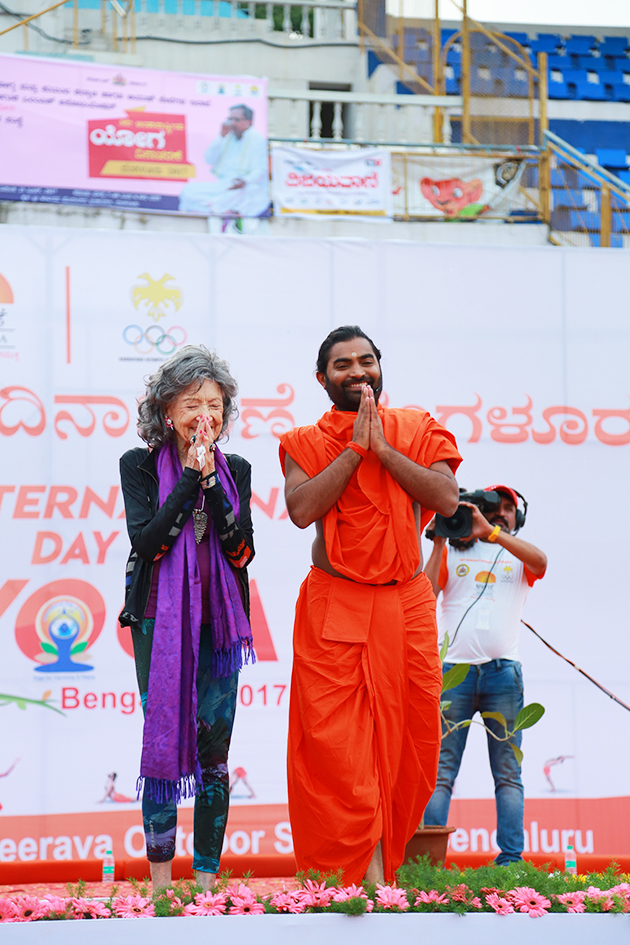 98-year-old yoga master Tao Porchon-Lynch and Shwaasa Guru on stage for International Day of Yoga at Kanteerava Outdoor Stadium in Bangalore, India - June 21, 2017