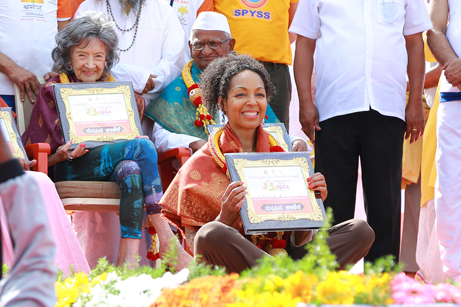 98-year-old yoga master Tao Porchon-Lynch and Teresa Kay-Aba Kennedy being honored on stage at International Day of Yoga at Kanteerava Outdoor Stadium in Bangalore, India - June 21, 2017