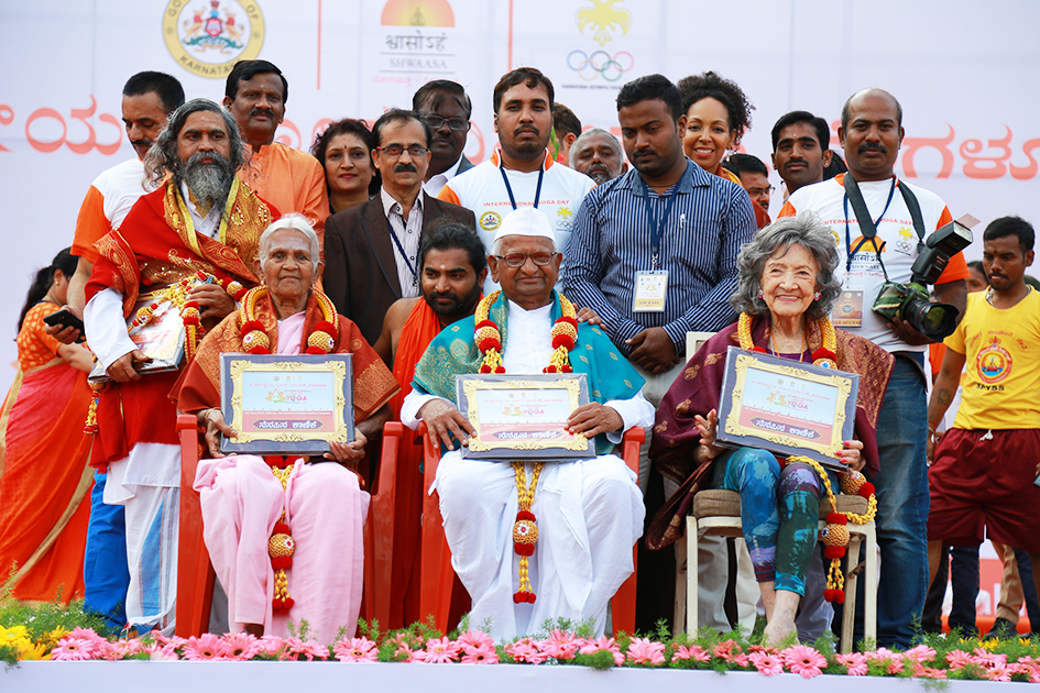 98-year-old yoga master Tao Porchon-Lynch, Anna Hazare and 97-year-old Amma V. Nanammal being honored on stage at International Day of Yoga at Kanteerava Outdoor Stadium in Bangalore, India - June 21, 2017