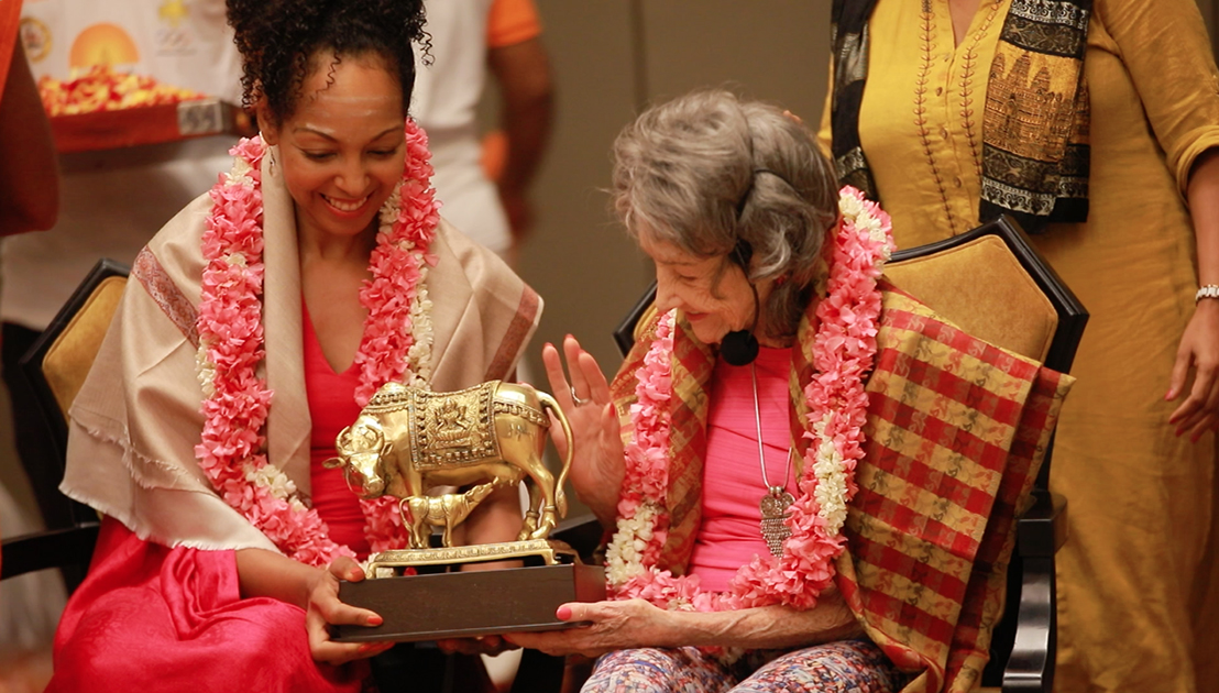 98-year-old yoga master Tao Porchon-Lynch with Teresa Kay-Aba Kennedy receiving a gift in a ceremony in Bangalore, India - June 24, 2017