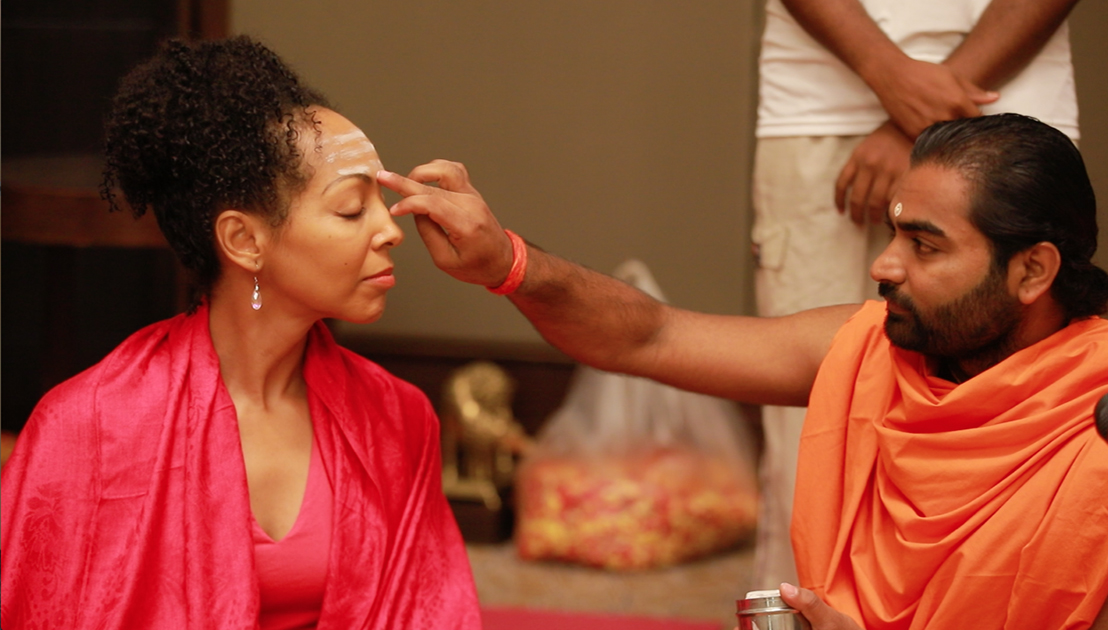 Shwaasa Guru putting Tripundra spiritual markings and bindu on the forehead of Teresa Kay-Aba Kennedy before Ishtalinga Meditation Bangalore, India - June 24, 2018