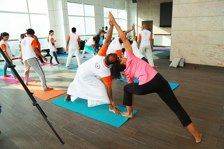 Teresa Kay-Aba Kennedy assisting 98-year-old yoga master Tao Porchon-Lynch teaching yoga in Bangalore, India - June 22, 2017